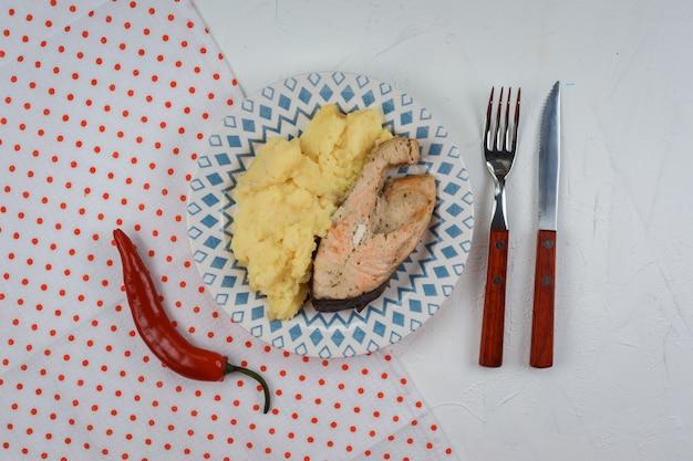 Kartoffelpüree mit lachssteak auf dem teller auf dem weißen hintergrund. polka dot serviette, chili, gabel und messer werden neben dem appetitlichen mittagessen serviert.
