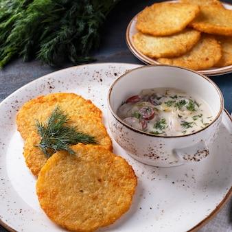 Kartoffelpuffer mit fleisch und sauerrahm. machanka mit würstchen. traditionelles belarussisches gericht.