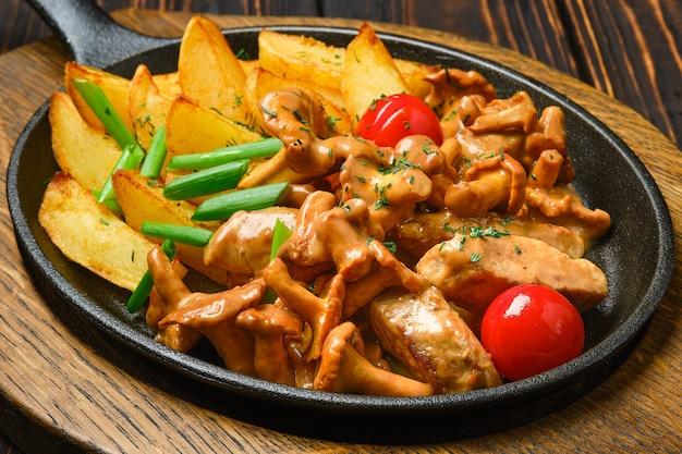 Kartoffelpuffer mit pfifferlingen und schweinefleisch in gusseiserner pfanne