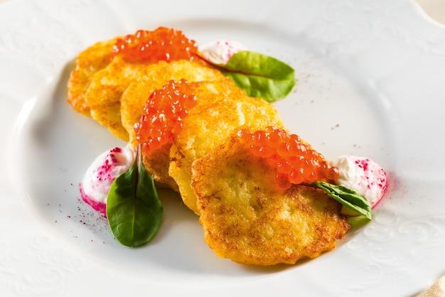 Kartoffelpuffer mit rotem kaviar unter saurer sahne und grünen blättern