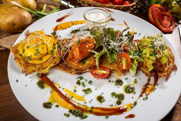 Kartoffelpuffer mit spiegeleiern, speck und gemüse zum frühstück