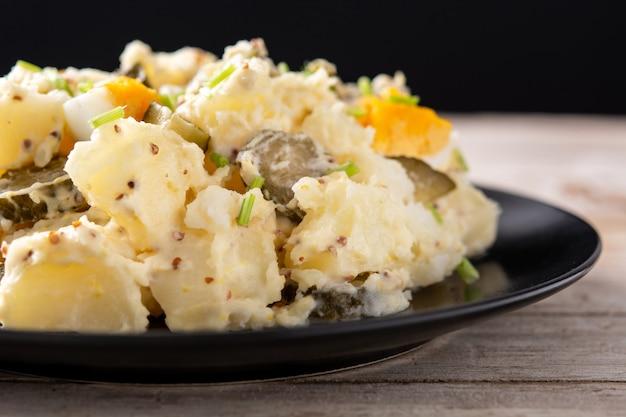 Kartoffelsalat mit gurken, ei und senf auf holztisch wooden