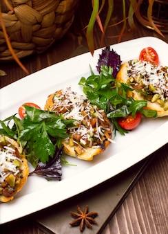 Kartoffelschalen beladen mit champignons, zwiebeln, kräutern, gemüse und geschmolzenem käse