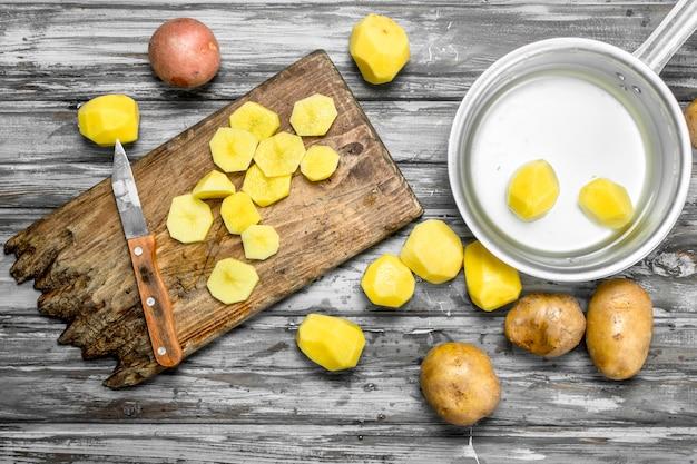 Kartoffelscheiben auf einem schneidebrett mit einem messer und geschälte kartoffeln in einem topf. auf holzoberfläche