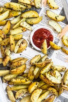 Kartoffelspalten mit ketchup auf einem tablett