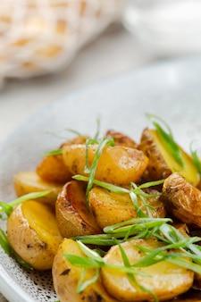 Kartoffelspalten, ofen geröstet nah oben auf hellem betonhintergrund. geröstete babykartoffeln. bratkartoffeln mit frühlingszwiebeln.