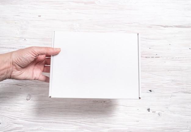 Karton aus weißem karton auf holzschreibtisch,