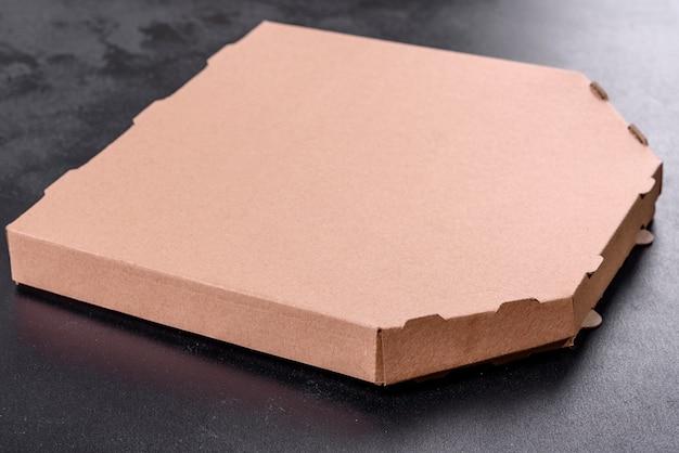 Karton braune schachtel mit quadratischer form für den transport und die lieferung von pizza. mediterrane küche