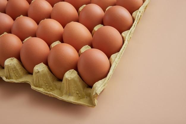 Karton der frischen eier auf beigem hintergrund