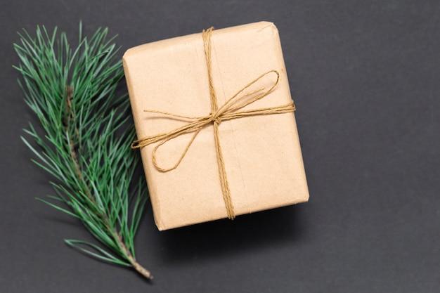 Karton geschenkbox für weihnachten oder jubiläum. warmes wintergeschenk mit handgefertigtem design und kiefer als detail. urlaubsstimmung im dezember. stilvolles geschenk für verschiedene anlässe.