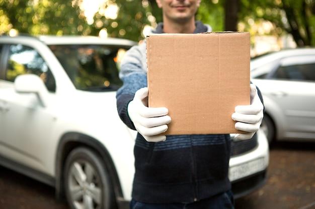 Karton in den händen eines kuriers in weißen handschuhen