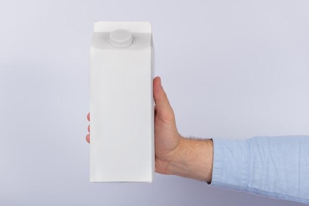 Karton milch oder saft in der hand auf weißem hintergrund. speicherplatz kopieren, verspotten