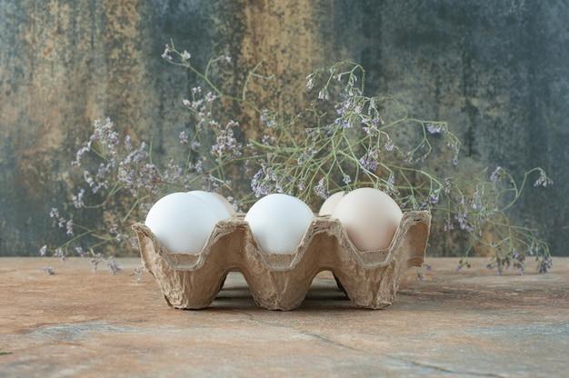 Karton mit frischen weißen eiern des huhns auf marmortisch.