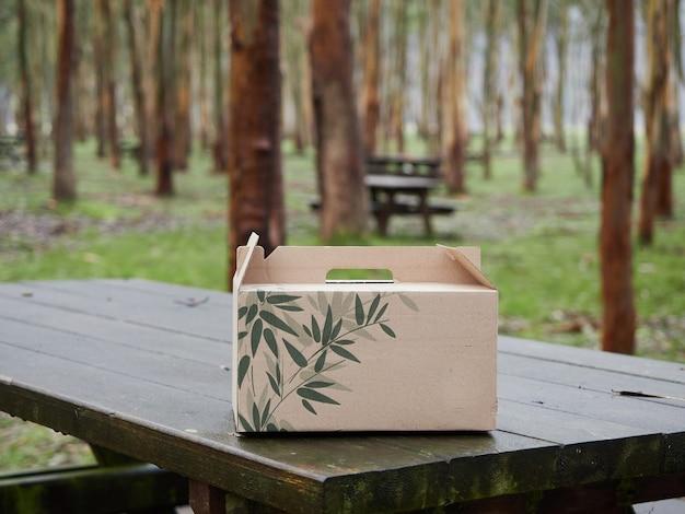 Karton mit grünen blättern auf einem hölzernen picknicktisch in einem wald mit bäumen im hintergrund