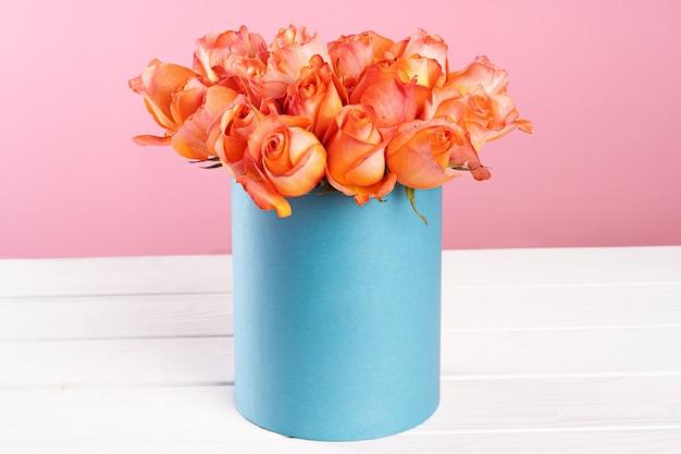 Karton mit rosen auf rosa oberfläche