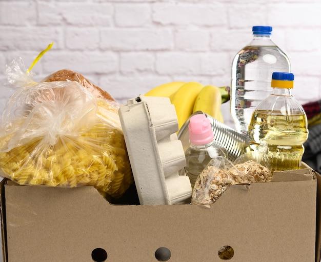 Karton mit verschiedenen produkten, früchten, nudeln, sonnenblumenöl in einer plastikflasche und konservierung. spendenkonzept