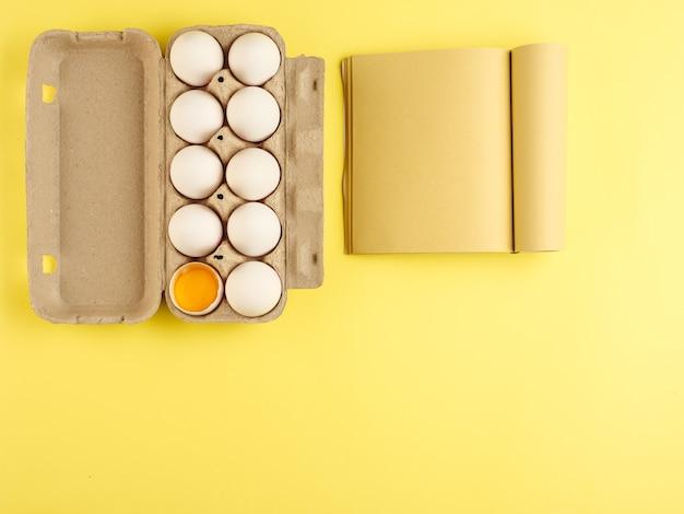 Karton mit weißen hühnereiern, bastelpapierbuch. von oben betrachten. speicherplatz kopieren.