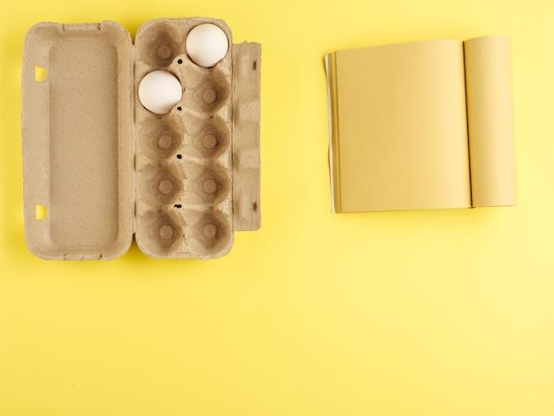 Karton mit weißen hühnereiern, bastelpapierbuch. von oben betrachten.