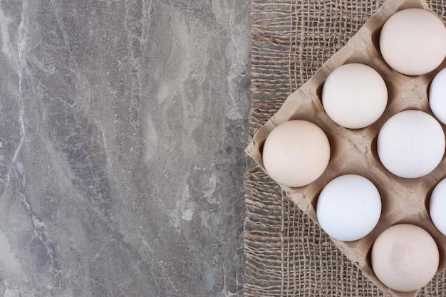 Karton mit weißen hühnereiern und federn. foto in hoher qualität