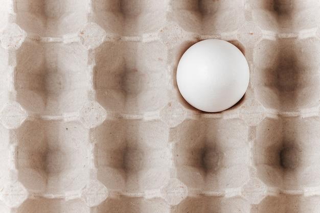 Kartonbehälter für eier mit einem ei in einer zellnahaufnahme.