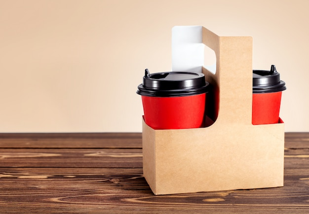 Kartonkorb mit zwei tassen kaffee auf holztisch zu gehen