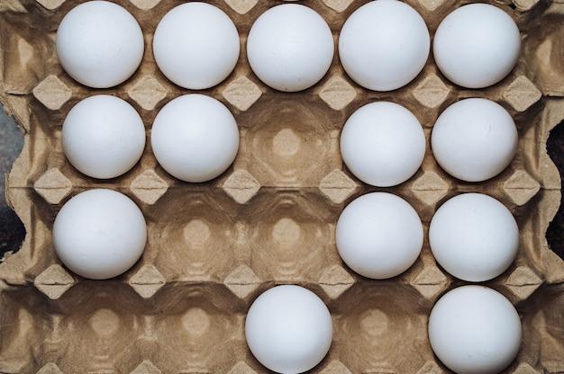 Kartonschale mit weißen hühnereiern. zellen in reihen mit eiern leeren