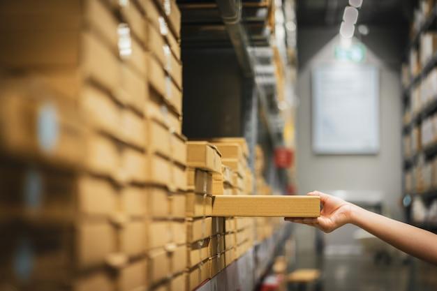Kartonverpackung mit unschärfehand der käuferfrau, die produkt vom regal im lager auswählt.