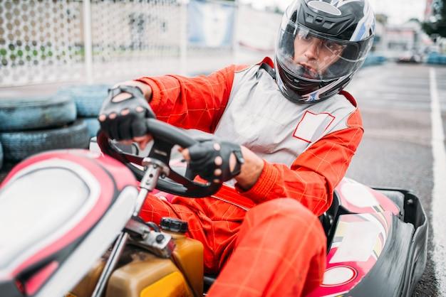 Kartrennen, fahren sie mit dem fahrer im helm auf der kartbahn. go-kart-rennfahrer