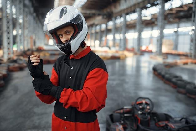 Kartrennfahrer in roter uniform, helm und handschuhen, kartsport im innenbereich.
