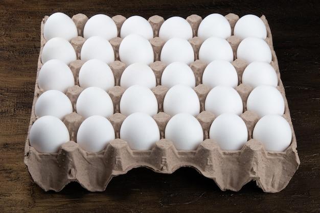 Kartusche mit weißen hühnereiern.