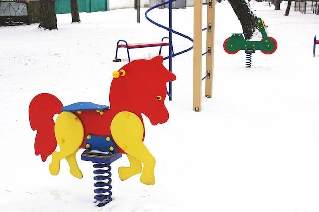 Karussell auf kinderspielplatz im winterwald