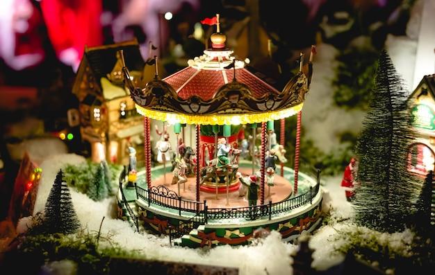 Karussell im miniaturspielzeug des europäischen weihnachtsmarktes. winter-heiligabend-szene mit traditionellen miniaturdorfhäusern. vintage spielzeugnachtstadt mit karussell.