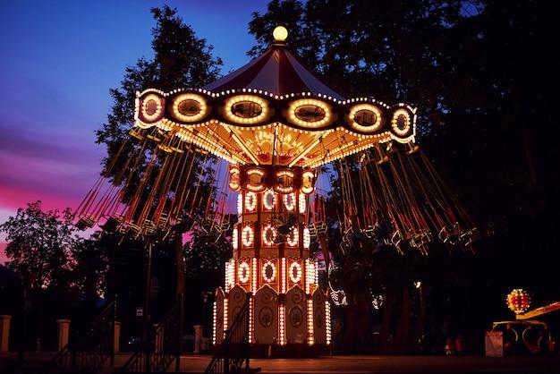 Karussell-karussell im vergnügungspark an der abendstadt