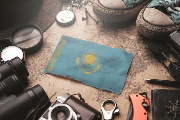 Kasachstan-flagge zwischen dem zubehör des reisenden auf alter weinlese-karte. touristisches bestimmungsort-konzept.