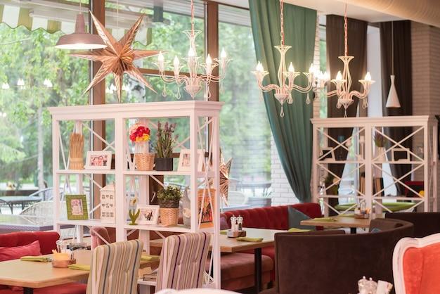Kasan, russland - 14. juli 2016: familiencafé anderson im gorki-park, intimer blick in cafés mit tischen, regalen, kronleuchtern, sofas