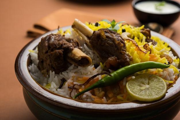Kashmiri mutton gosht oder lamm biryani zubereitet in basmati-reis serviert mit joghurt-dip über stimmungsvollem hintergrund, selektiver fokus