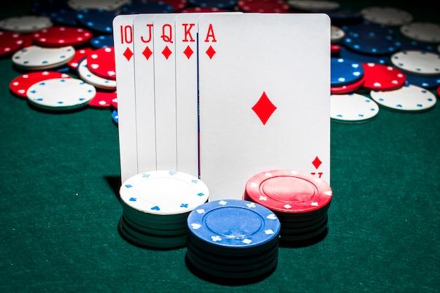 Kasinochips stapeln vor spielkarte des königlichen errötens