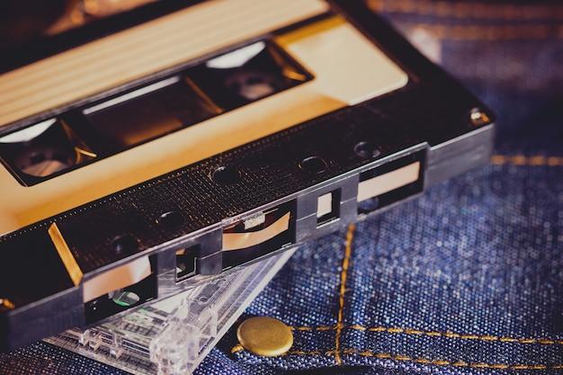 Kassette auf jeansstoff in der dunkelheit. von vintage 90er jahre musik-player.