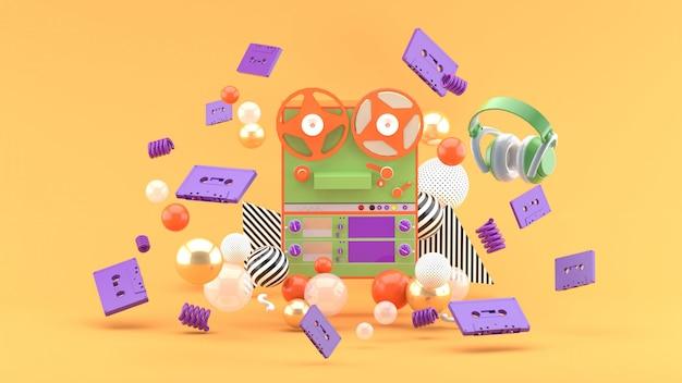 Kassettenrekorder zwischen den bändern und kopfhörern auf der orange. 3d-rendering.
