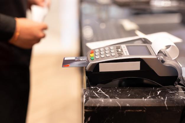 Kassierer, der kreditkartenmaschine für kundeneinkaufszahlung im speicher verwendet.
