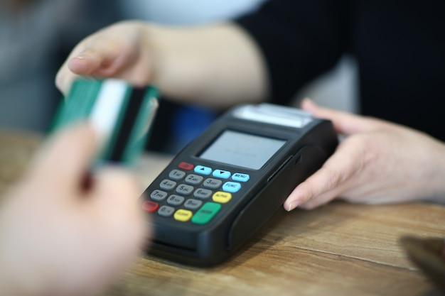 Kassierer-hand, die plastikkreditkarte zur zahlung nimmt