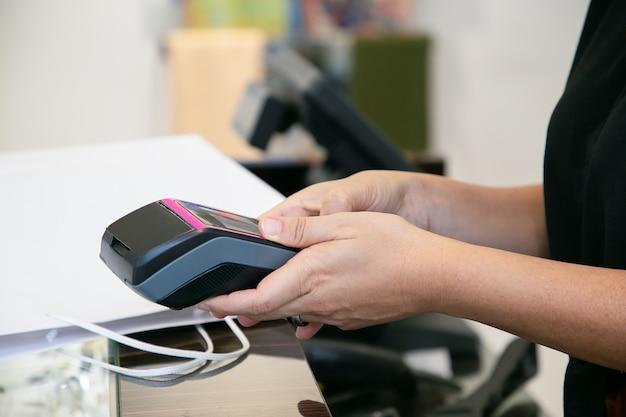 Kassierer oder verkäufer, der den zahlungsvorgang mit pos terminal und kreditkarte durchführt. kurzer schuss, nahaufnahme der hände. einkaufs- oder kaufkonzept