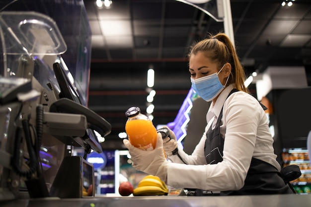 Kassiererin im lebensmittelgeschäft mit maske und handschuhen, die vollständig gegen das koronavirus geschützt sind
