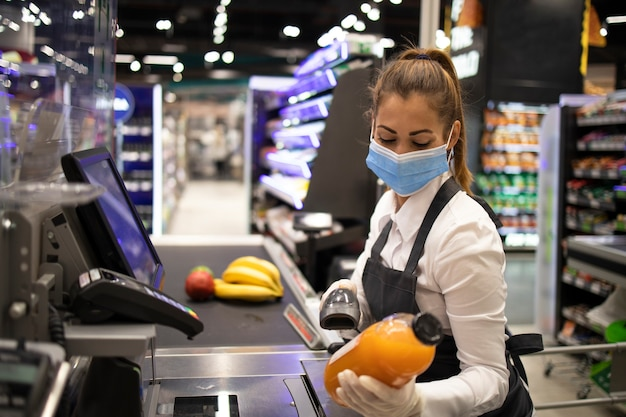 Kassiererin im supermarkt mit maske und handschuhen, die vollständig gegen das koronavirus geschützt sind