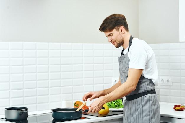 Kassiererschürzen des männlichen küchenchefs in der küche, die lebensmittelprofi zubereitet
