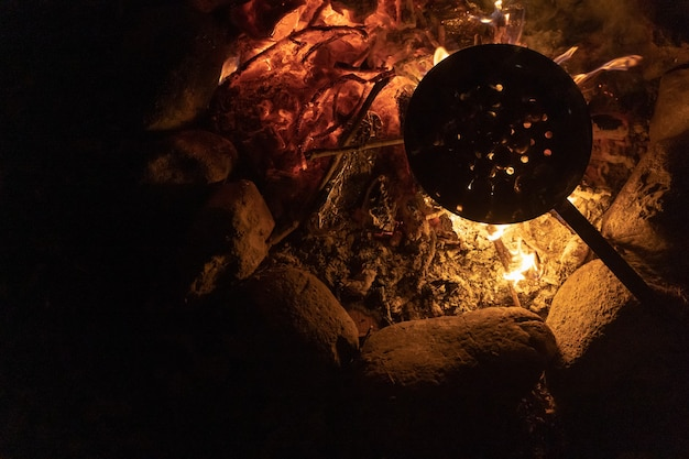 Kastanien kochen an einem warmen und gemütlichen lagerfeuer im wald teichfeuer im urlaub beim camping