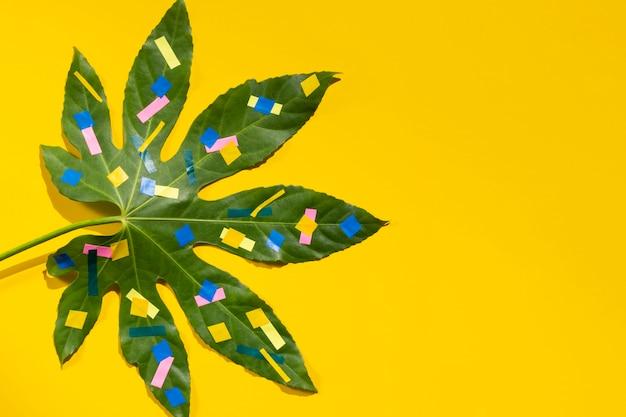 Kastanienblatt mit punkten und gelbem kopienraumhintergrund