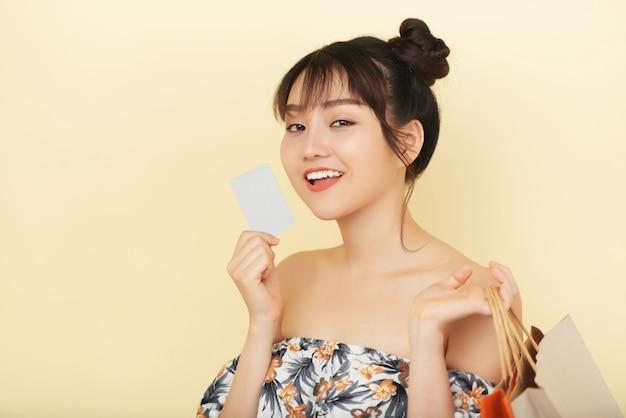 Kasten herauf den schuss der jungen frau eine bankkarte mit einkaufstaschen in ihrer anderen hand halten