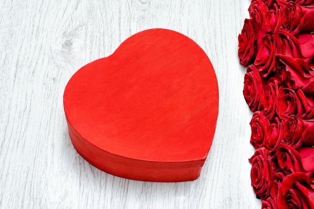 Kasten in form eines herzens auf einem hellen holztisch und einem blumenstrauß von rosen