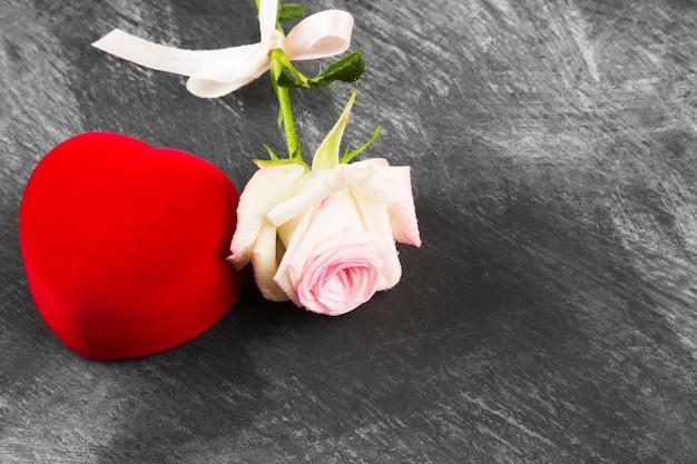 Kasten mit einem ring und einer rosarose auf einem dunklen hintergrund. kopieren sie platz